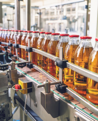Conveyor belt, juice in glass bottles on beverage plant or factory interior, industrial manufacturing production line